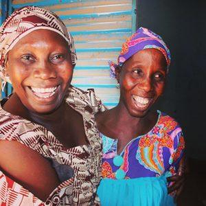 Two women in Senegal smiling, in a Tostan partner community